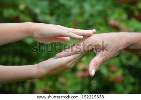 Two hands together against the green natural background