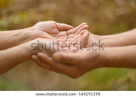 Two hands together against the natural backgrouns