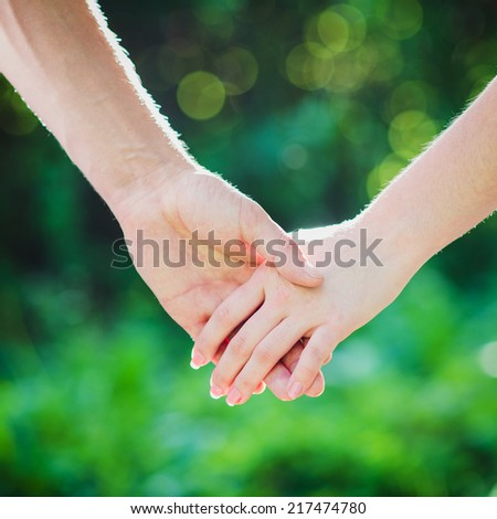 Two hands together on green background