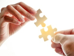 two hands trying to connect couple puzzle piece with sunset background.Business strategy teamwork, problem solving concept. Teamwork is collaborative effort of team to achieve goal or complete mission