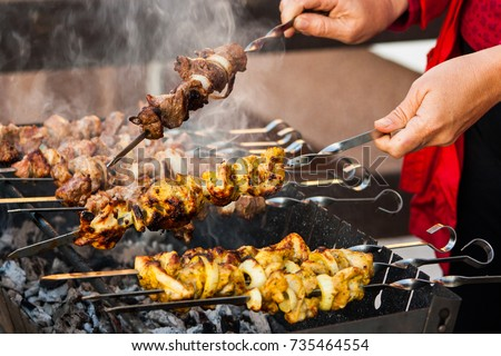 Two hands turning skewers with pieces of juicy fragrant steaming meat over a hot fuming brazier. Homemade. Street food.