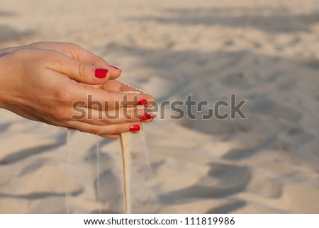 Two hands with sand and red nails