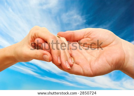 Two hands - woman and man touch each other in delicate, subtle way on sky background