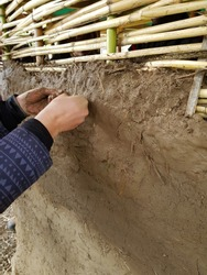 Two hands work on a bamboo structured clay house with natural materials