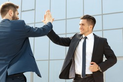 Two handsome business colleagues high fiving outdoors