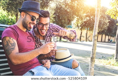 Two handsome friends taking a selfie with a smart phone sitting on a bench on a sunny day looking the camera making funny face