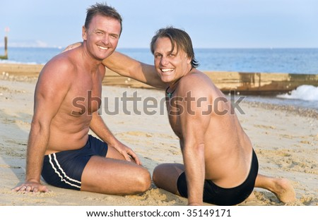 stock photo : Two handsome mature gay men having fun on beach.