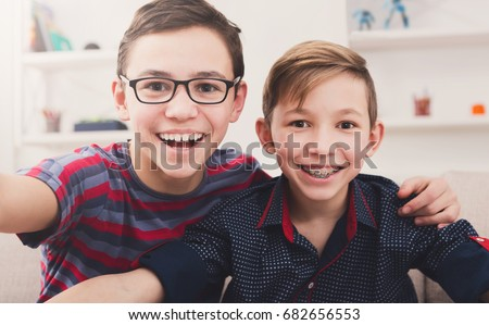Two handsome teenage boys taking selfie while posing with smile to phone at home. Wearing glasses and braces. Friendship, brotherhood and health care concept