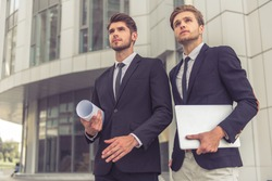 Two handsome young businessmen in classic suits with rolled paper with plan and a laptop are looking upward anf examining building, standing outdoors