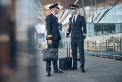 Two handsome young men airline workers in protective face masks waiting for flight at airport
