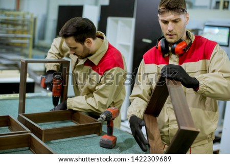 Two handsome young workers assembling furniture in the factory