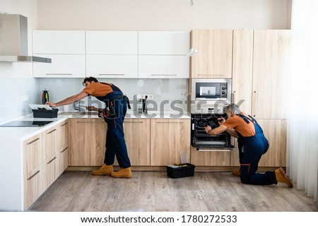 Two handymen, workers in uniform fixing, installing furniture and equipment in the kitchen, using screwdriver indoors. Furniture repair and assembly concept. Horizontal shot