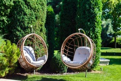 Two hanging chairs in a garden on sunny summer day. Place for outdoor recreation