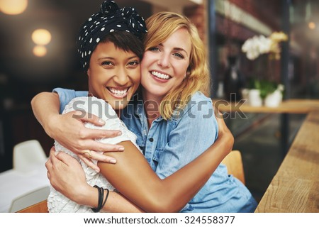 Two happy affectionate young woman hugging each other in a close embrace while laughing and smiling, young multiracial female friends