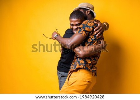 Two happy African American friends hug and laugh after a long time apart. Isolated on yellow background