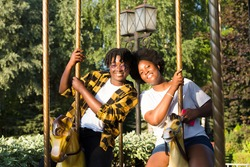two happy African-American women in a park on an amusement ride in the summer.