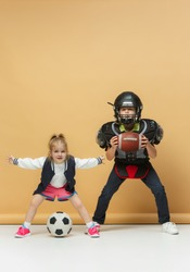 Two happy and beautiful children showing different sport. Studio fashion concept. American football and tennis players. Children's fashion show. Sport style. Teen and kids fashion concept. children's