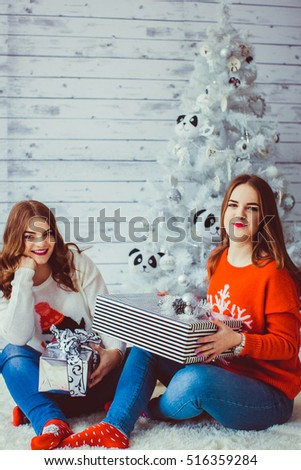 Two happy and beautiful sisters sitting near the Christmas tree #516359284