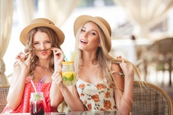 Two happy beautiful girls having fun in a cafe in sunny summer day. Lifestyle, travel concept.