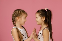 two happy beautiful little girls in dress looking at each other on pink background. children friendship. kids playing