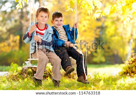 Two happy boy swinging on a swing in a sunny autumn day