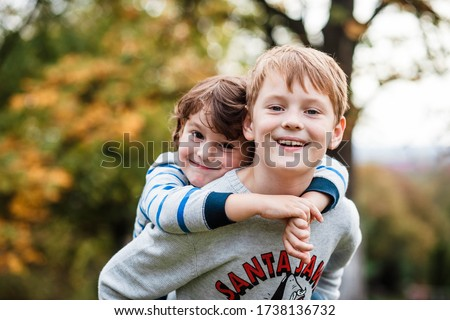 Two happy boys, happy brothers who are smiling happily together. Brothers play outdoors in summer, best friends. Little brother with brother on his back. Two brothers in the woods. Fraternal relations Foto stock ©