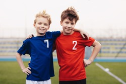 Two happy boys outdoor in sportswear. Children smiling to camera. Kids standing on sports grass field. Sports education for children
