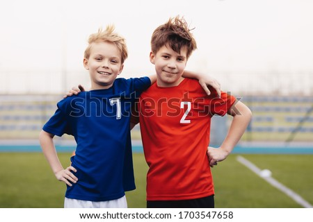 Two happy boys outdoor in sportswear. Children smiling to camera. Kids standing on sports grass field. Sports education for children Stock foto ©