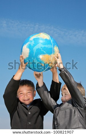 Two happy boys wear in suits holding the globe together