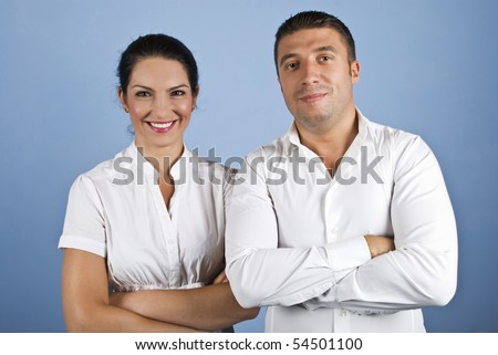 Two happy business man and woman standing with arms crossed and smiling dressed in white shirts on blue background