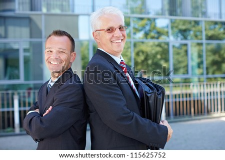 Two happy business people leaning on each other back to back