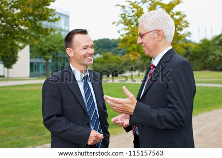 Two happy business people talking with each other in a park