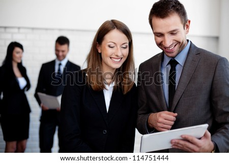 Two happy business people working with digital tablet