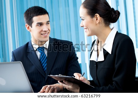 Two happy businesspeople working together at office. Focus on woman.