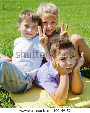 Two happy children doing joke over boy outdoor