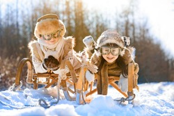 Two happy children go sledding in winter. Sunny wintry day. Retro vintage clothes and glasses.