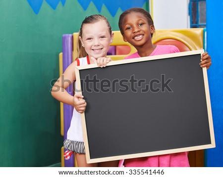 Two happy children holding an empty chalkboard in preschool