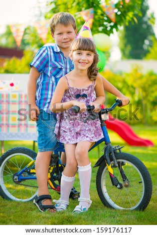 Two happy children in love sitting on bicycle