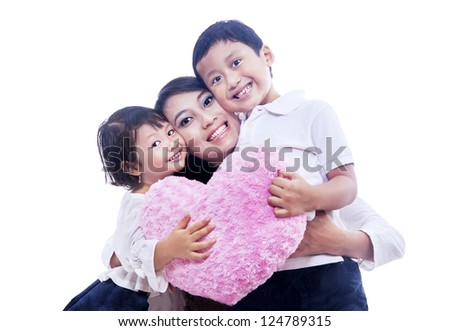 Two happy children is giving their mom a hug while holding pink pillow on isolated white background