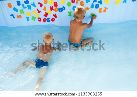 Two happy children play in swimming pool with plastic letters for bathroom. Brothers are happy together in warm water on sunny summer day. Concept of teaching games for preschoolers. Copy space text #1133903255