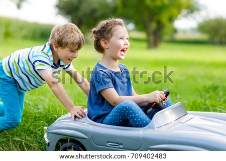 Two happy children playing with big old toy car in summer garden, outdoors. Boy pushing car with little girl inside. Laughing and smiling kids. Family, childhood, lifestyle concept.