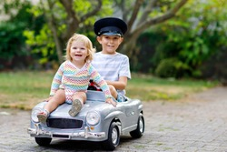 Two happy children playing with big old toy car in summer garden, outdoors. Kid boy driving car with little toddler girl inside. Laughing and smiling kids. Family, childhood, lifestyle concept