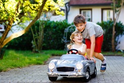 Two happy children playing with big old toy car in summer garden, outdoors. Kid boy pushing and driving car with little toddler girl, cute sister inside. Laughing and smiling kids. Lovely family