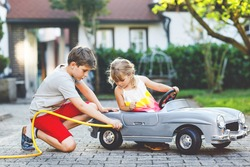 Two happy children playing with big old toy car in summer garden, outdoors. Kid boy refuel car with little toddler girl, cute sister inside. Boy using garden hose and fill  with gasoline, sibling game