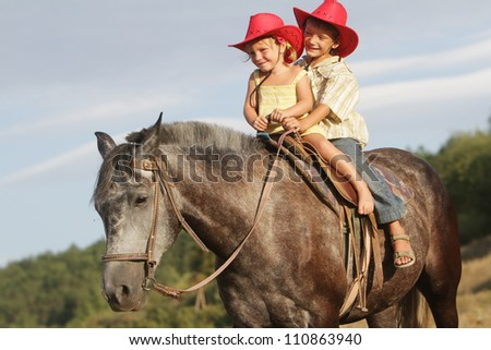 two happy children riding horse on natural background