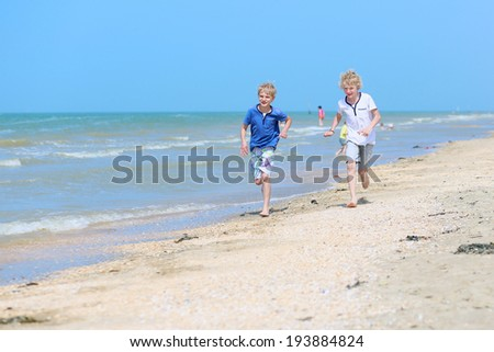 Two happy children, twin brothers, blonde school boys playing on the beach running along the sea shore on a sunny summer day