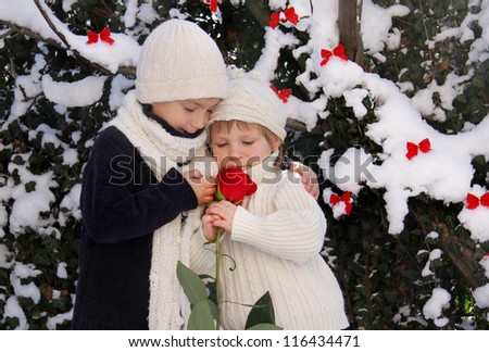 two happy children with red rose on natural winter background