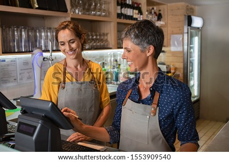 Two happy coffeehouse waitresses in apron smiling and working on cash register. Mature and smiling women working behind the counter of coffee shop. Two happy waitresses working at cafeteria. Photo stock ©