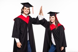 Two happy college graduates giving high five smiling after receiving diplomas on white background.