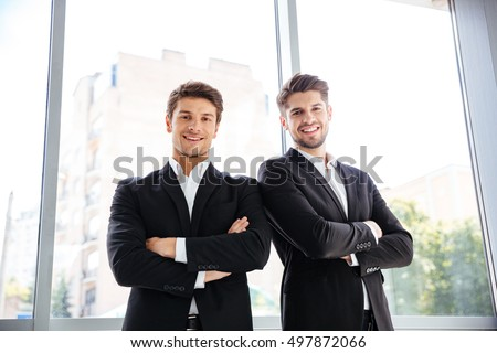 Two happy confident young businessmen standing with arms crossed in office